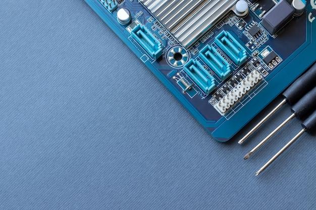 Scheda madre del computer e tre piccoli cacciaviti su carta grigia