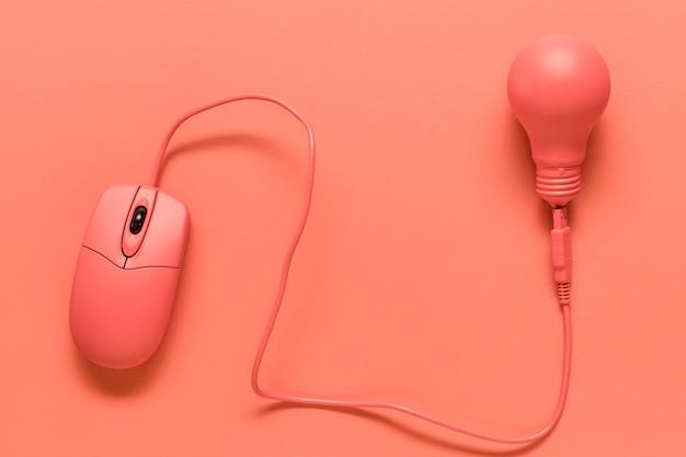 Mouse del computer collegato alla lampada sulla superficie colorata Foto Premium