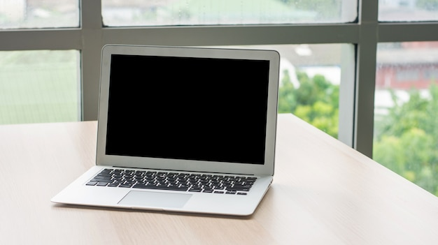 Schermo del computer portatile con specifiche di copia vuote sulla scrivania in ufficio, computer portatile