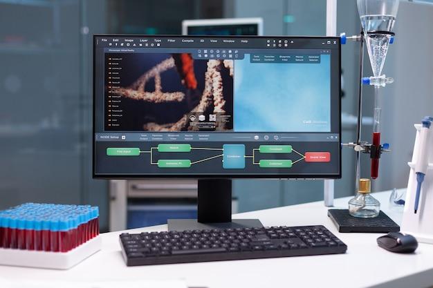 Computer in piedi sul tavolo con la ricerca microbiologica in mostra durante l'esplorazione biochimica farmaceutica...