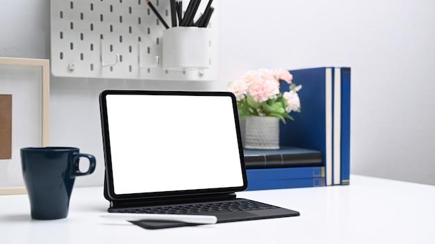 Tablet computer con schermo vuoto, tazza di caffè e articoli per ufficio sulla scrivania bianca.