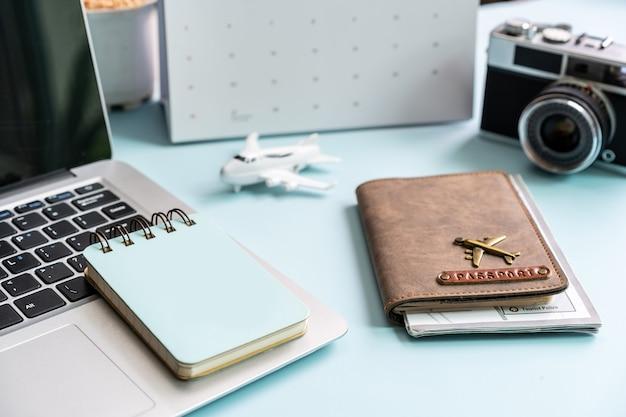 Computer con calendario e articoli da viaggio su sfondo a colori con spazio di copia, concetto di pianificazione delle vacanze