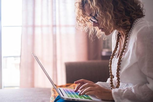 Donna caucasica adulta concentrata che lavora su un laptop seduto sul divano di casa - concetto di moderno nomade digitale lavoratore libero - donna d'affari con tastiera colorata che digita e scrive