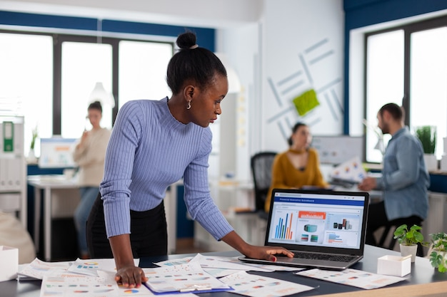 Donna d'affari nera africana concentrata che scorre attraverso le statistiche sul laptop in piedi. diversi team di uomini d'affari che analizzano i rapporti finanziari dell'azienda dal computer. start up di successo