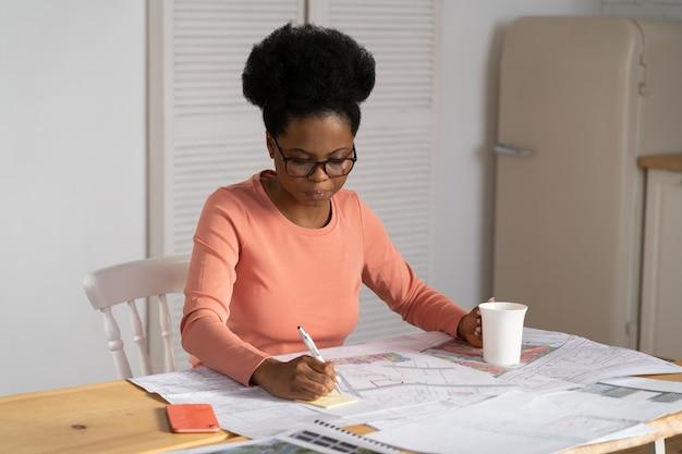 La donna concentrata dell'architetto disegna il progetto del lavoro a casa la designer femminile nera crea il piano del progetto