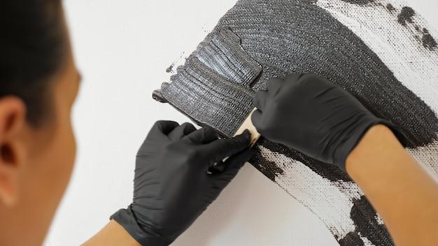 L'artista concentrato in guanti neri disegna un'immagine di colore grigio con una speciale piccola spatola artistica su tela bianca a casa vista ravvicinata