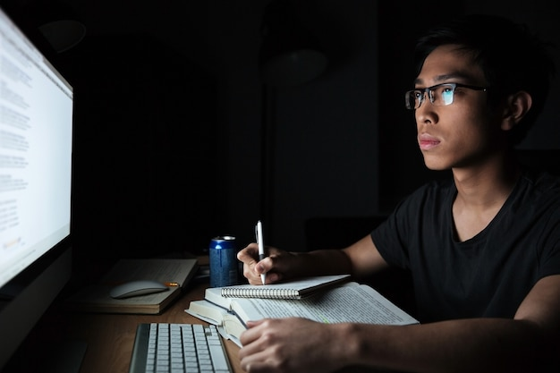 Giovane asiatico concentrato che scrive nel blocco note e usa il computer in una stanza buia