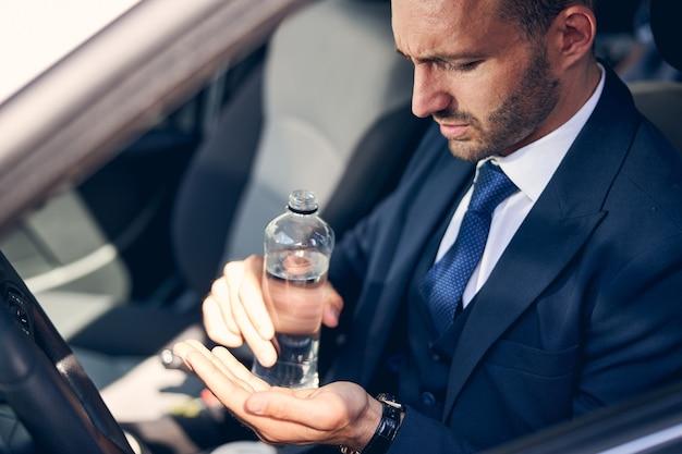 Uomo barbuto concentrato che arriccia la fronte mentre è immerso nei pensieri, seduto nella sua comoda auto