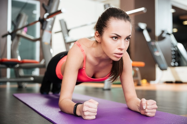 Bella giovane sportiva concentrata che fa esercizio della plancia sulla stuoia in palestra