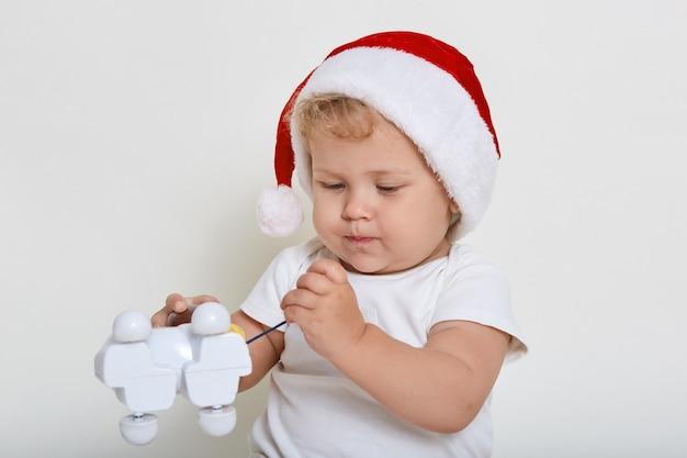Infante dai capelli biondi concentrato studiando il suo nuovo giocattolo, regalo di natale, tenendo in mano il giocattolo di plastica del cane