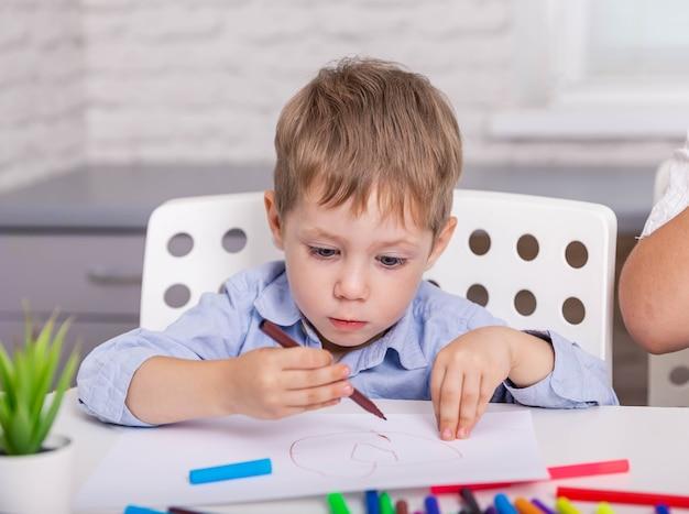 Immagine concentrata del disegno del ragazzo con con il pennarello a casa