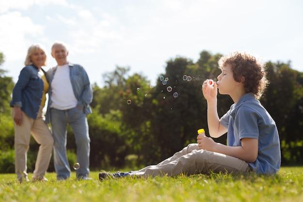 Ragazzo concentrato tenendo la bottiglia con il sapone nella mano sinistra e seduto in posizione semi sull'erba verde