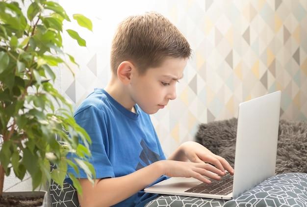 Ragazzo concentrato seduto alla scrivania con computer portatile e fare i compiti