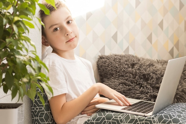 Ragazzo concentrato seduto alla scrivania con il computer portatile e fare i compiti