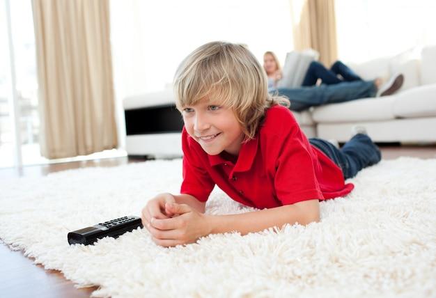 Ragazzo concentrato che guarda tv che si trova sul pavimento