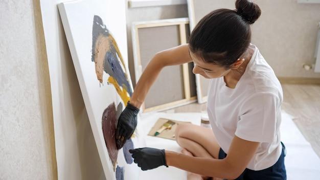 Bruna concentrato con panino in maglietta bianca e pantaloncini neri disegna foto che corrono le mani con vernici su tela in officina in estate