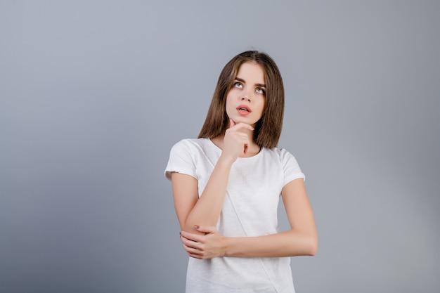 Donna concentrata del brunette che pensa esaminando copyspace isolato sopra grey