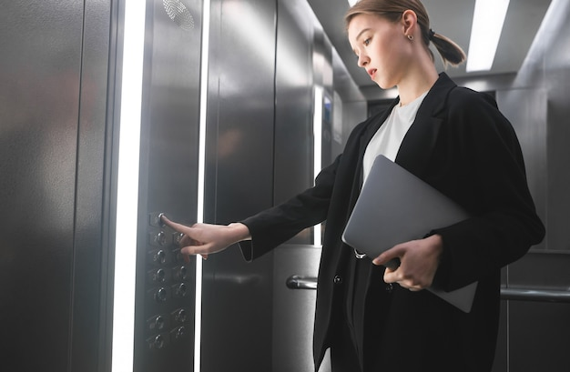 Imprenditrice concentrata premendo il pulsante dell'ascensore tenendo il laptop in mano.