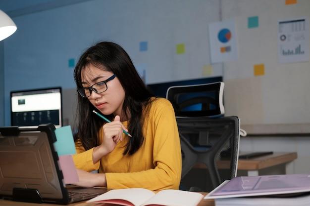 Donna d'affari concentrata che lavora fino a tardi con il suo computer portatile.
