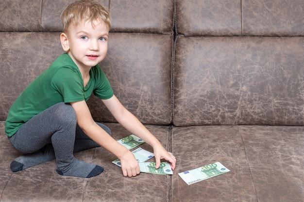Il bambino caucasico concentrato in abiti casual tiene in mano cento euro e conta i soldi sul divano della stanza, vista laterale, spazio copia. educazione finanziaria ed economica dei bambini