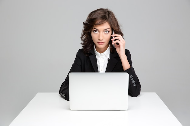 Donna d'affari carina e fiduciosa concentrata che lavora usando il laptop e parla al cellulare