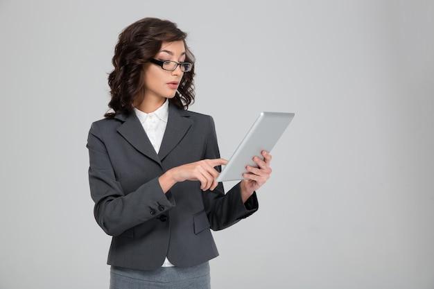 Concentrato fiducioso piuttosto giovane donna d'affari in bicchieri utilizzando tablet
