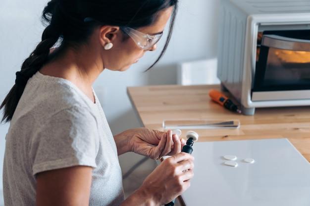 Artigiana concentrata che lavora da casa realizzando gioielli fatti a mano e indossando occhiali protettivi.