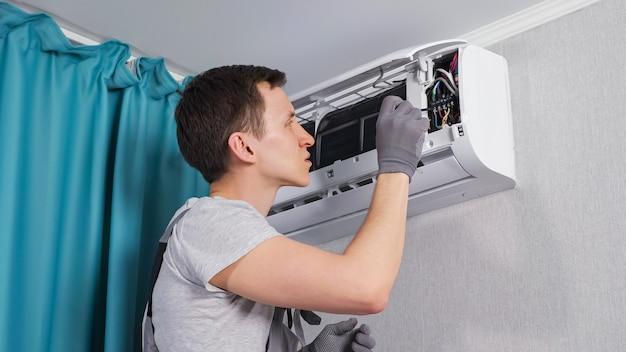 L'elettricista concentrato ripara il pannello del circuito elettrico con il cacciavite nell'unità del condizionatore d'aria sulla parete vicino alle tende nel primo piano della stanza