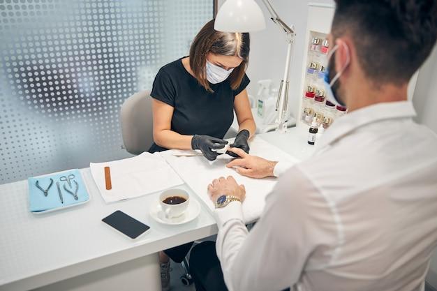 Persona di sesso femminile concentrata che china la testa mentre lima le unghie prima di fare la pulizia