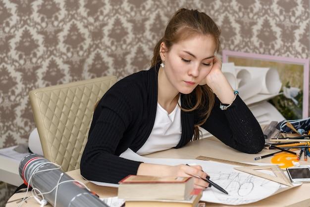 Schizzi concentrati del disegno dell'architetto della studentessa sulla tela bianca che si siede per il desktop.