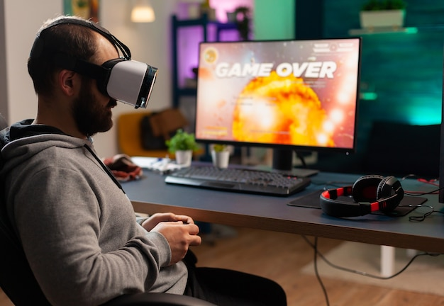 Giocatore concentrato che indossa le cuffie per la realtà virtuale che perde i giochi sparatutto spaziale online. giocatore sconfitto che usa il controller per la competizione online a tarda notte nella sala da gioco