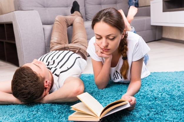 Ragazza concentrata che legge un libro vicino al suo ragazzo sdraiato su un tappeto nel loro soggiorno in un'atmosfera rilassata