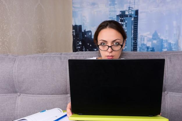 Ragazza concentrata con gli occhiali che sbircia dietro il laptop mentre lavora e fa i suoi affari da casa con in mano una penna
