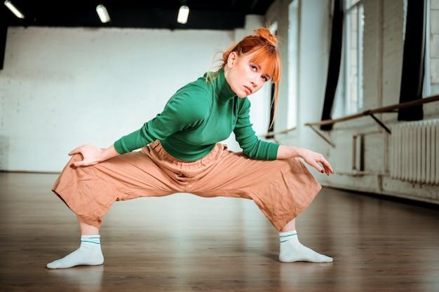 Concentrato. allenatore di yoga snello e di bell'aspetto con un dolcevita verde che sembra concentrato mentre fa asana