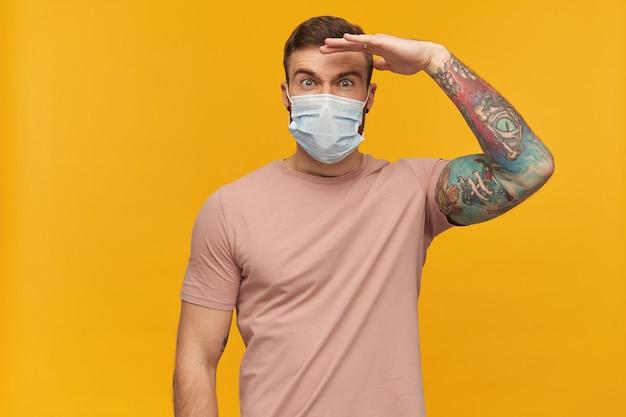 Concentrato bel giovane uomo barbuto con il tatuaggio nella maschera igienica per prevenire l'infezione tiene la mano sopra la testa e guarda lontano davanti isolato sopra il muro giallo