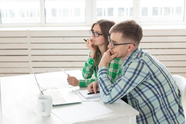 Marito e moglie concentrati contano gli acquisti e le bollette dell'ultimo mese e registrano i risultati nella contabilità domestica su un taccuino e su un laptop. concetto di risparmio e contabilità.
