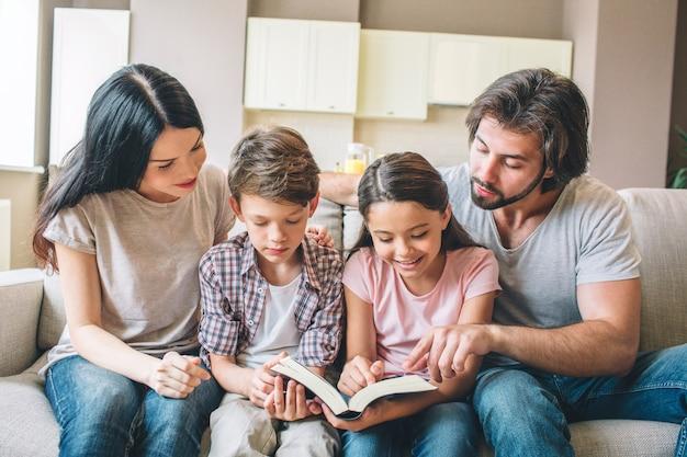 I bambini concentrati sono seduti sul divano con i genitori e leggono un libro