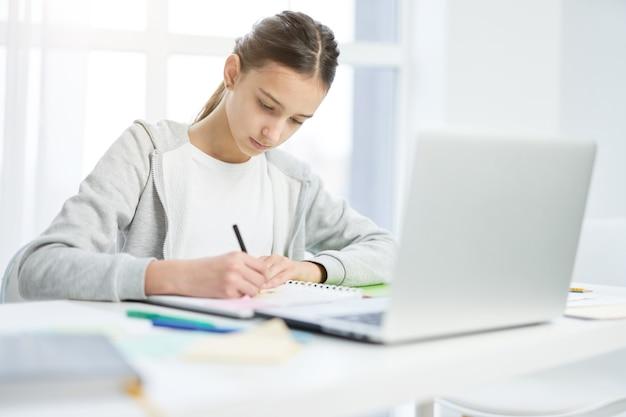 Adolescente latina concentrata che prende appunti nel suo blocco note, usando il laptop mentre ha lezione online a casa. istruzione a distanza, concetto di scuola a casa