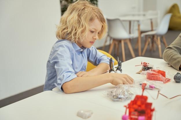Ragazzino caucasico concentrato seduto al tavolo ed esaminando i dettagli di un giocattolo tecnico