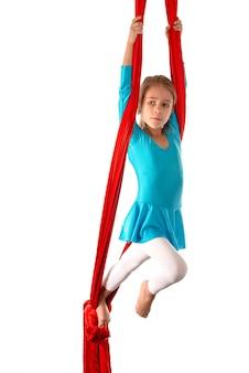 Piccola ragazza caucasica concentrata in un costume da bagno blu fa esercizi ginnici su un nastro aereo rosso su un bianco