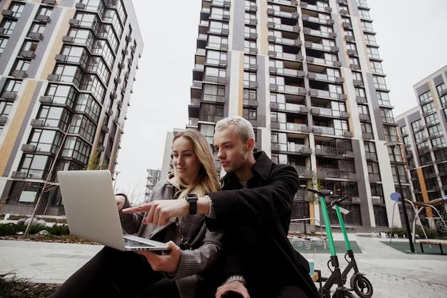 L'uomo concentrato aiuta la sua ragazza con il problema del computer portatile. giovani coppie che si siedono fuori e che lavorano al computer portatile. sono venuti qui con gli scooter. concetto di trasporto ecologico.
