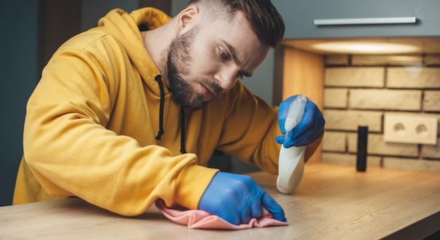 Uomo concentrato con la barba sta pulendo un tavolo con uno spray disinfettante a casa