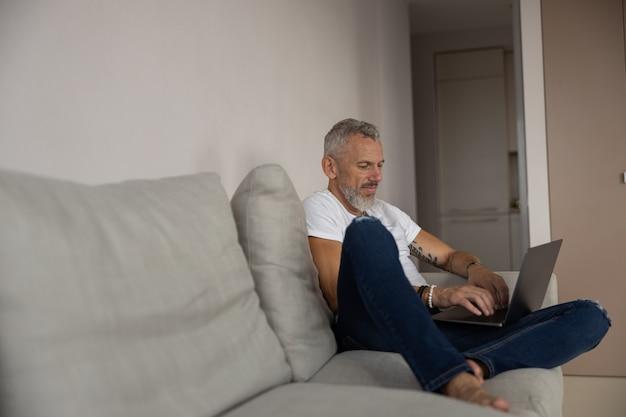 Uomo concentrato che lavora al suo laptop su un divano