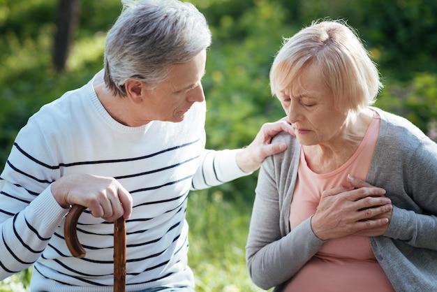 Donna senior immobile concentrata che tocca il suo petto e che ha attacco di cuore mentre suo marito si preoccupa per lei e si siede sulla panchina all'aperto