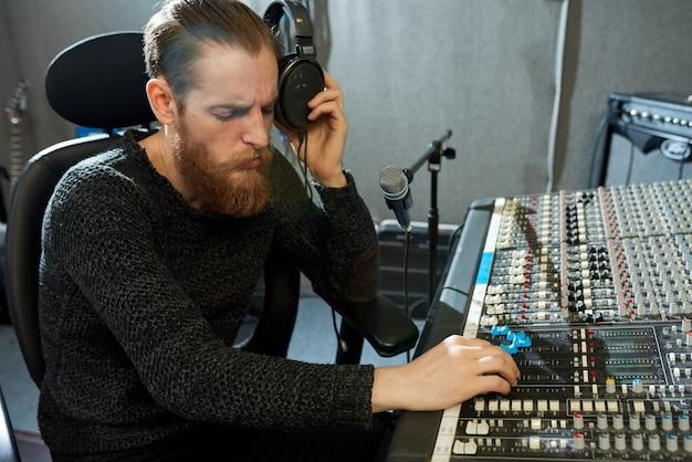 Progettista musicale concentrato che regola i suoni in studio Foto Premium
