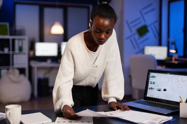 Donna d'affari afroamericana oberata di lavoro concentrata che analizza i grafici di profitto dei documenti finanziari