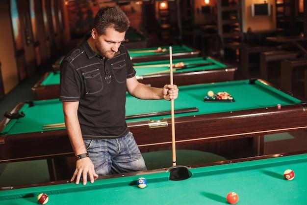 Giocatore concentrato con una stecca nella sala da biliardo.