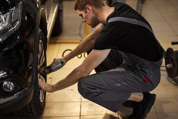 L'uomo professionista concentrato del meccanico auto ripara una ruota che si è rotta