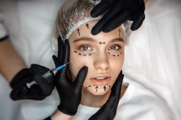 La giovane donna concentrata e rilassata che si trova sullo strato e guarda diritto. il suo viso è segnato. siringa da una mano per l'iniezione. un'altra faccia a tre tocchi.