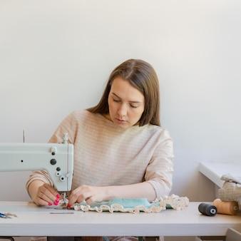 Sarta concentrata che cuce vestiti nel suo atelier di moda